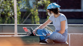 A person sits on a bench while working on a laptop