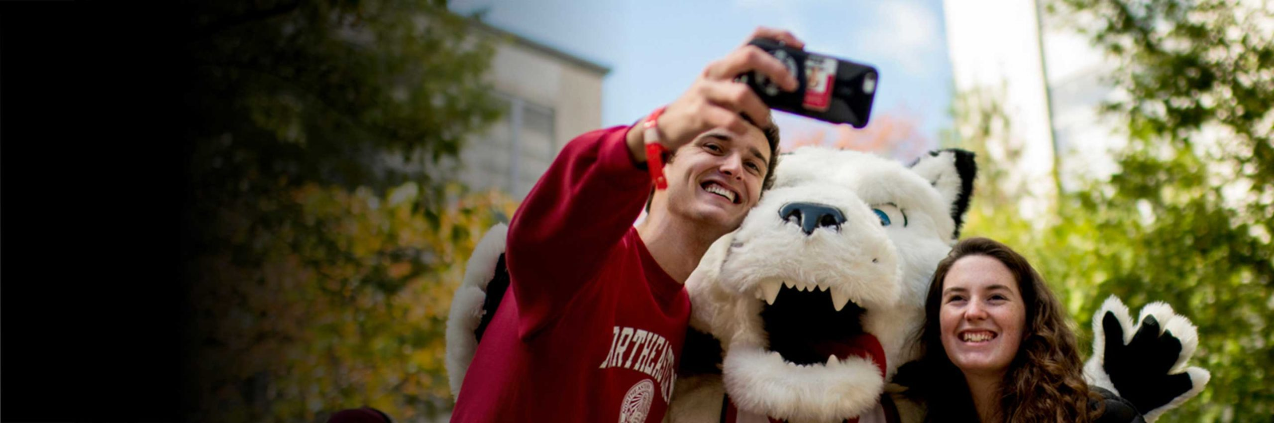 Students take a selfie with Paws the husky