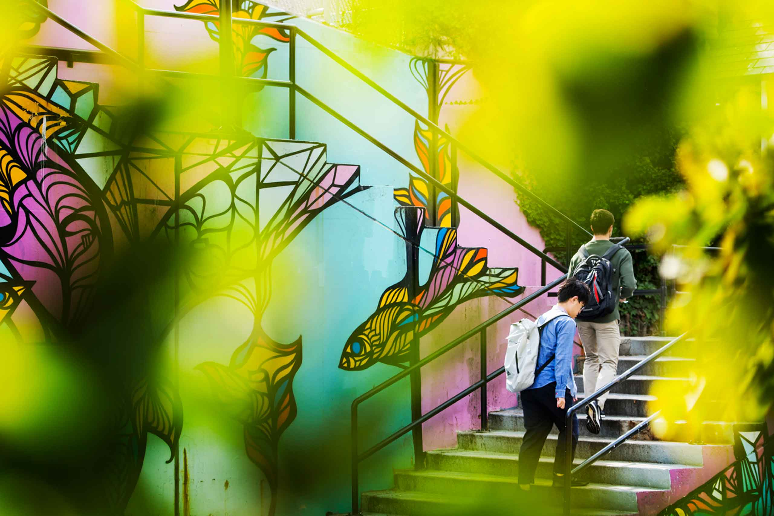 students walk up a stairway decorated with a colorful mural