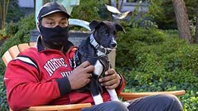 Jordan Clark seated with his dog, Riou