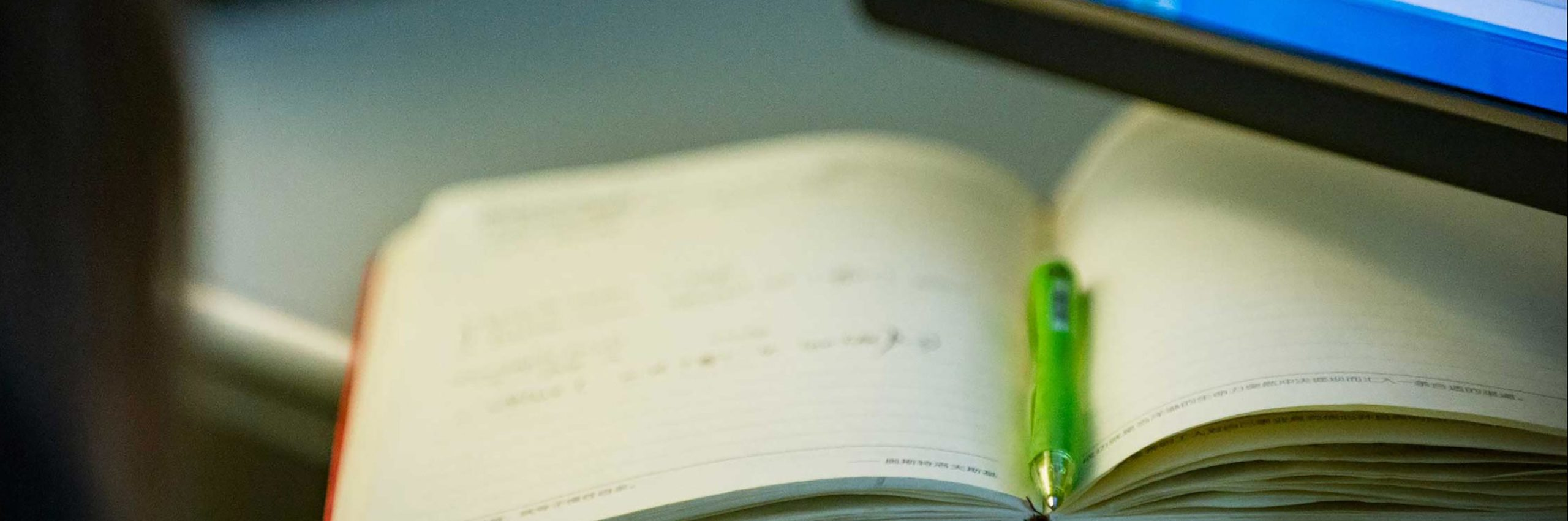 a pen rests on a notebook